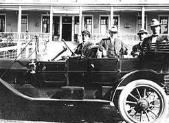 Chauffeur Harry Stevens and guests in the 1912 Mitchell touring car that taxied visitors to and from the Canyon View Hotel, located at the site of today's Cleveland Dam, ca. 1914. NVMA 6724